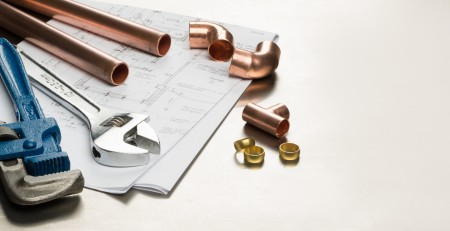 Various plumbers tools and plumbing materials including copper pipe, elbow joint, wrench and spanner.