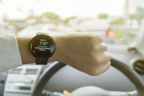 Close up of man in car on road watching smartwatch and using application navigation map to destinationClose up of man in car on road watching smartwatch and using application navigation map to destination