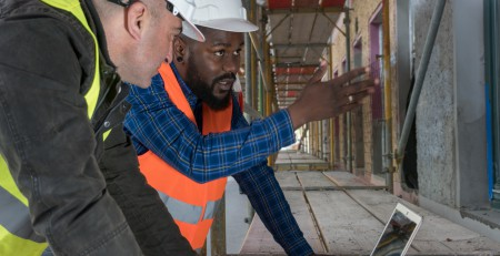 Two construction workers, an African american and a white, wearing orange and yellow safety jackets and helmets among scaffolding on construction site. One explaining innovative electrician tricks