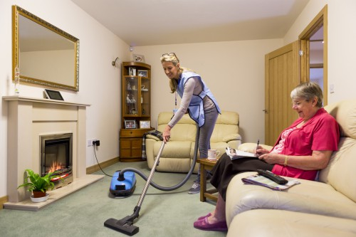 Female carer is hoovering the living room to help an elderly woman. The woman is sitting on a sofa relaxing. Cleaning service business