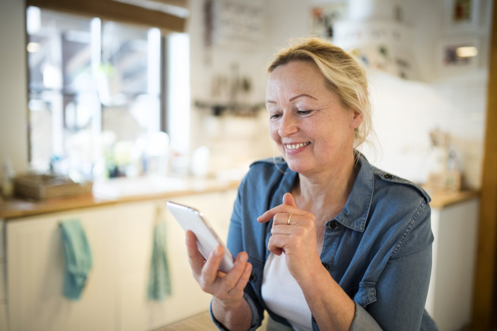Beautiful senior woman at home in her kitchen holding texting customer support on a smart phone, writing or reading something, smiling.